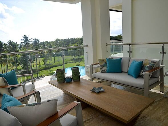 A private balcony with two outdoor couches and a table overlooking our golf course